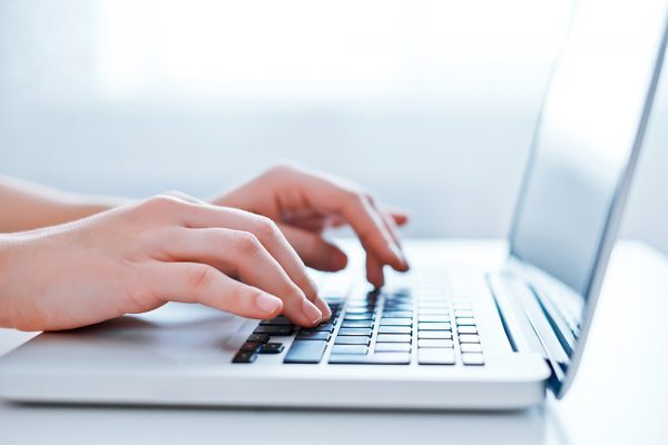 Woman's hands using laptop at the office. Close-up image